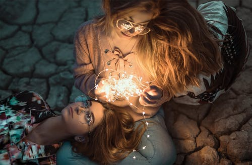 High-angle Photo of Two Women with String Lights