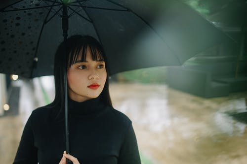 Photo of Woman Holding Black Umbrella