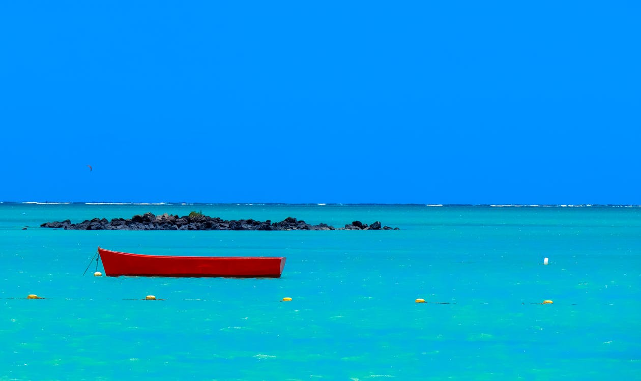 Red Wooden Boat in the Middle of Body of Water