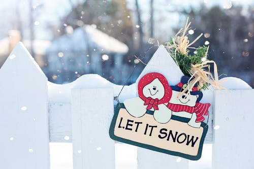 Let It Snow Signage Hanging on Fence