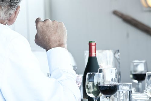 Man Sitting Near Wine Bottle and Glasses