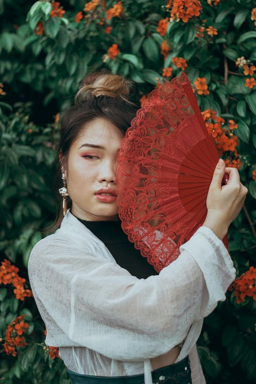 Woman Holding Red Hand Fan Near Green Leaf Plant