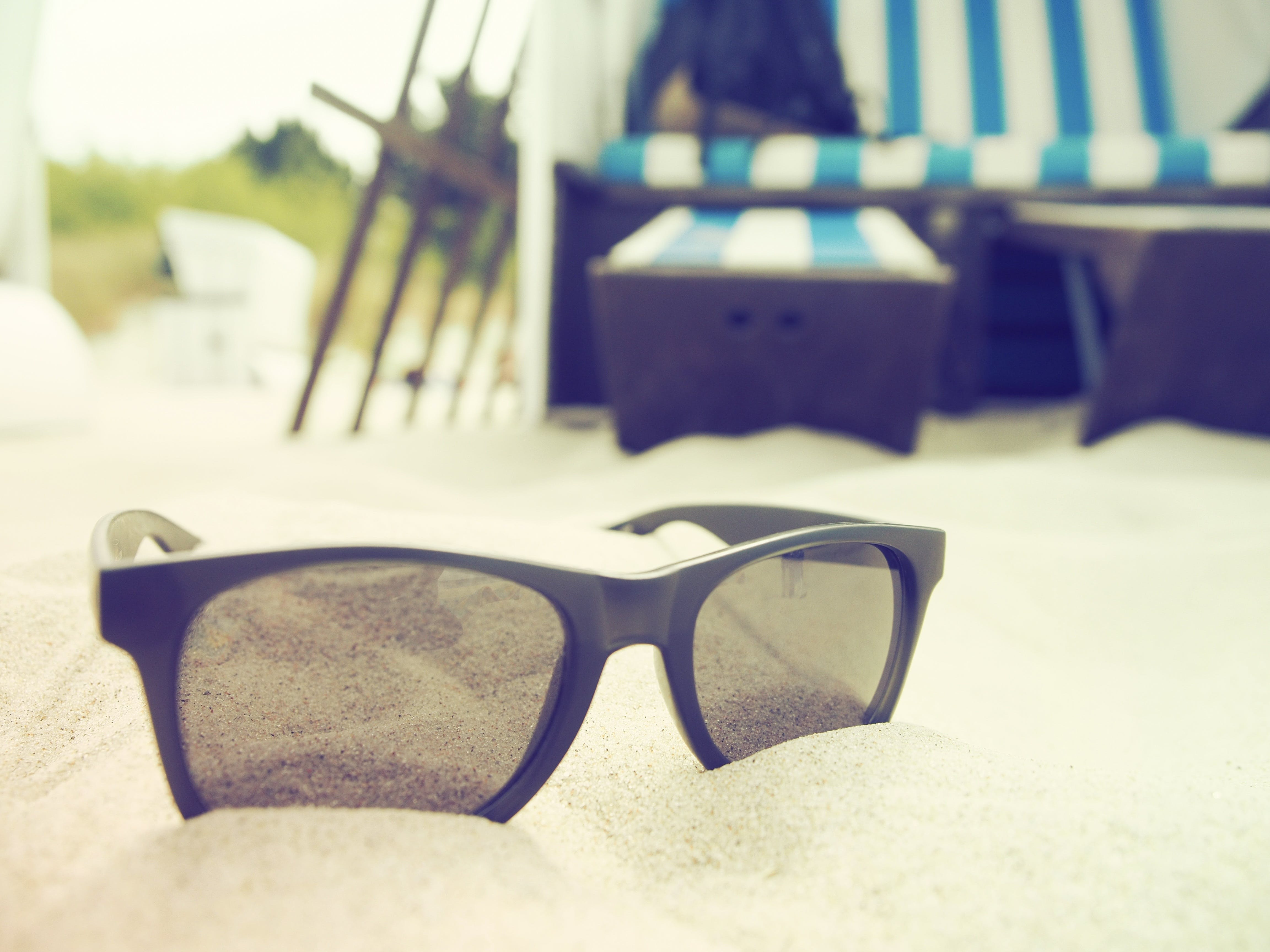 Selective Focus Photography of Black-framed Sunglasses on Sand