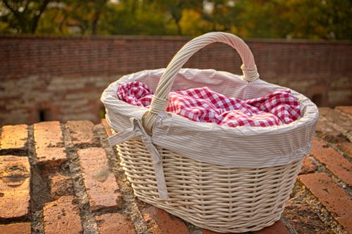 White Wicker Basket on Brick Surface
