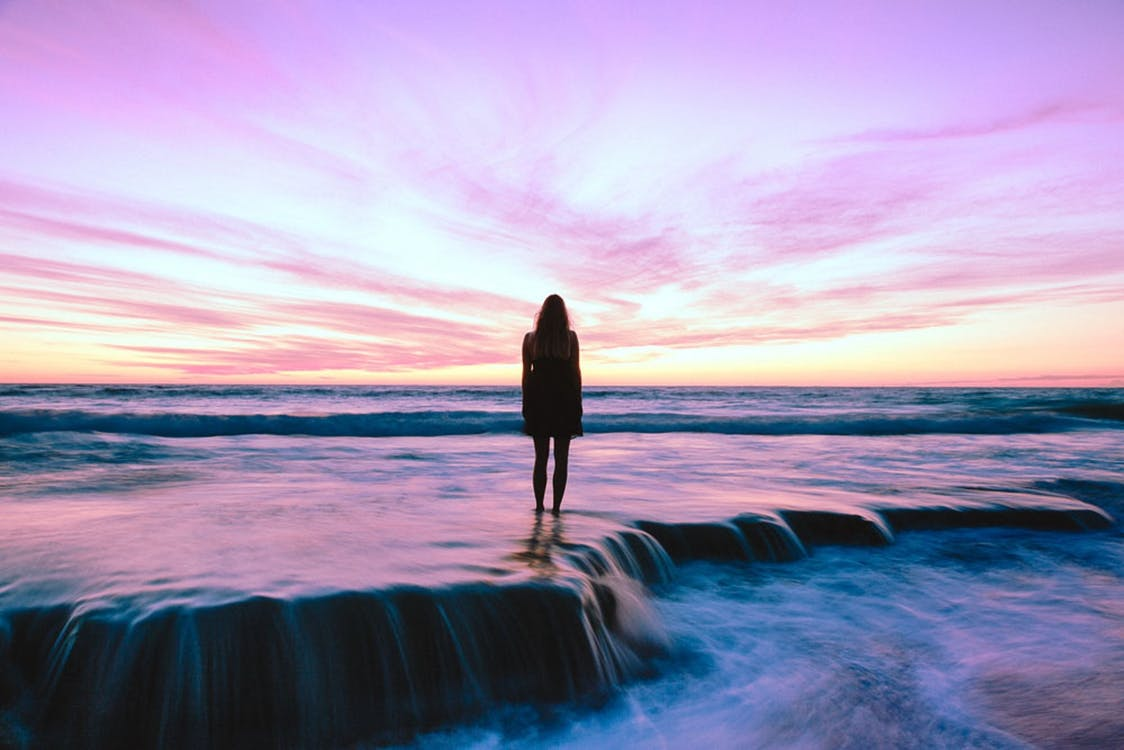 Silhouette Photography of Woman Standing on Seashore during Golden Hour