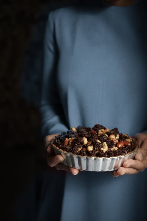 Person Holding Chocolate Pie with Nuts