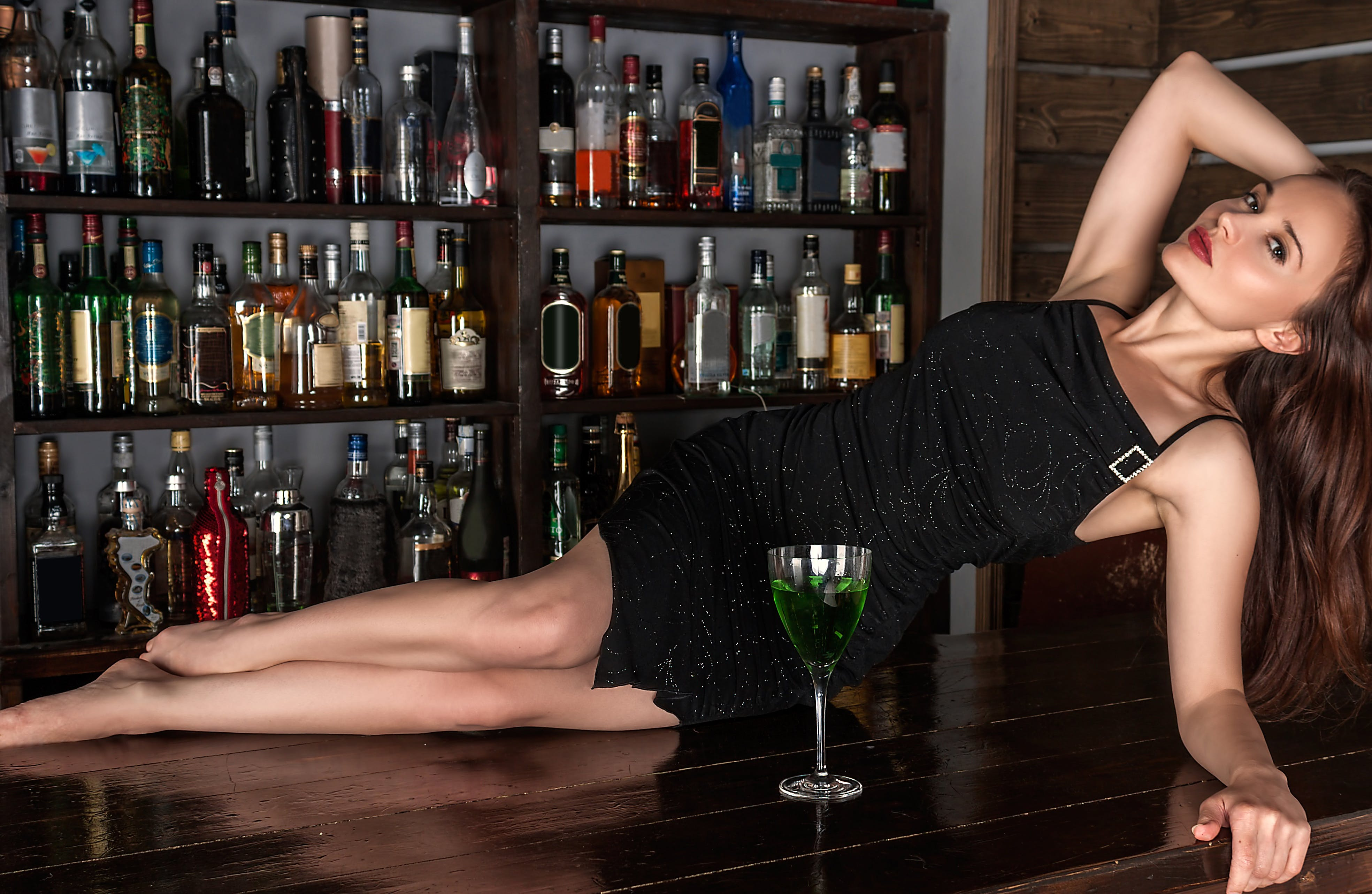 Woman in Black Dress Lying on Bar Table