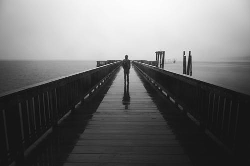 Grayscale Photography of Person Standing on Bridge