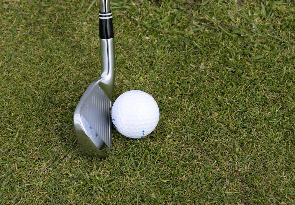 Silver wedge golf club beside a ball. | Photo: Pexels