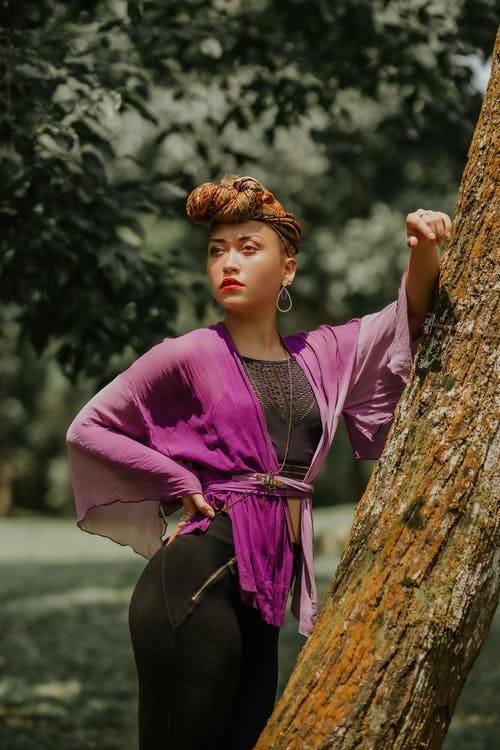 Woman Wearing Purple Dress Standing in Front of Tree