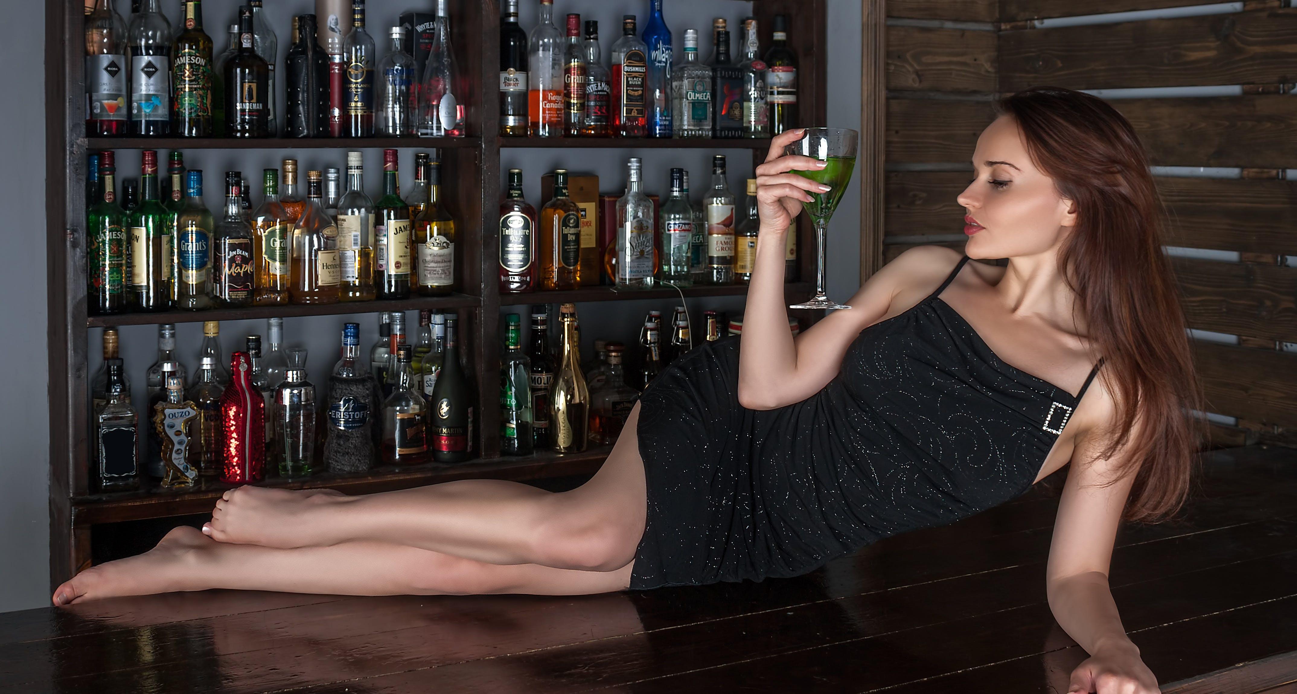 Woman in Black Spaghetti Strap Lying on Desk in Front of Liquor Bottles