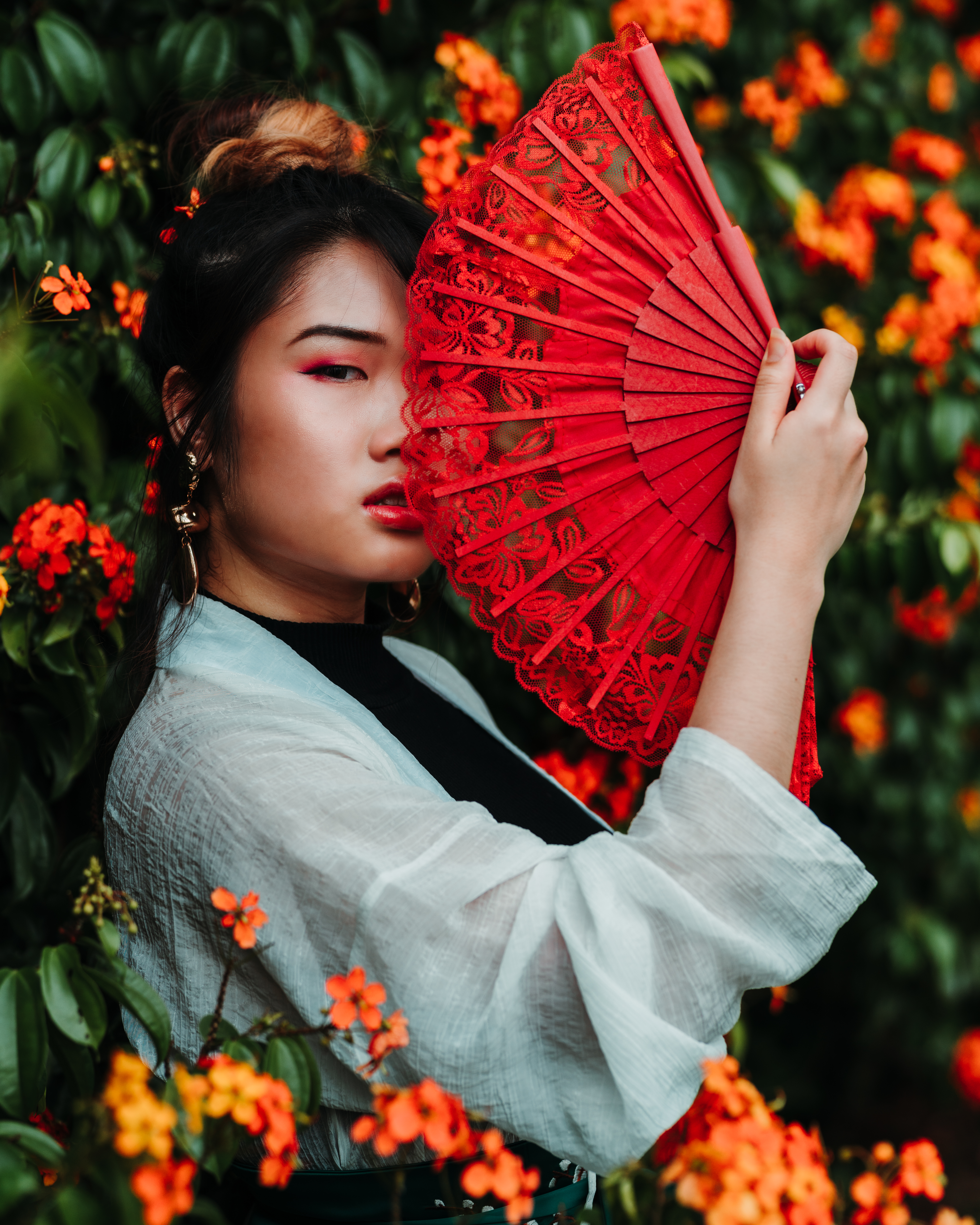 Woman Holding Red Fan Beside Plant With Flowers