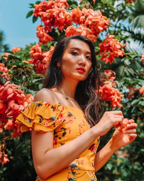 Attractive woman in garden against flowering bush