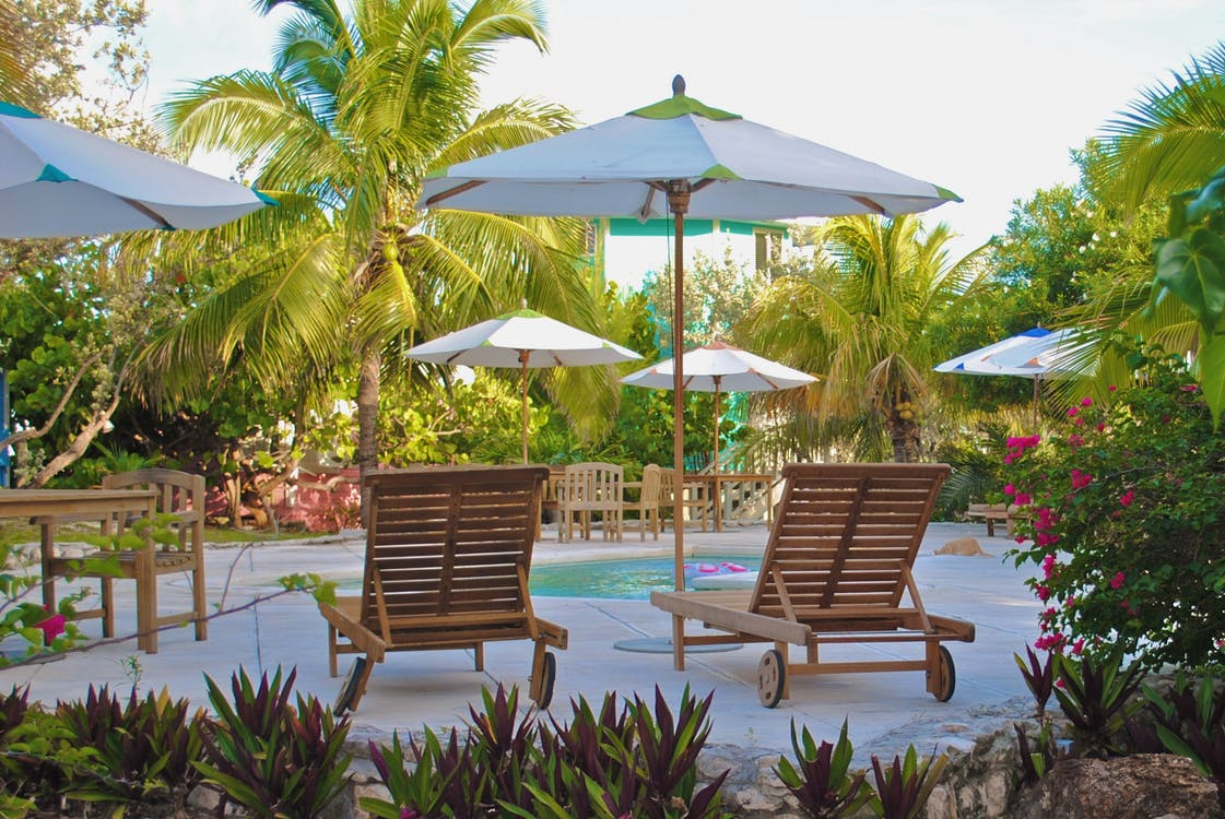 Two Brown Wooden Lounge Chairs at the Pool