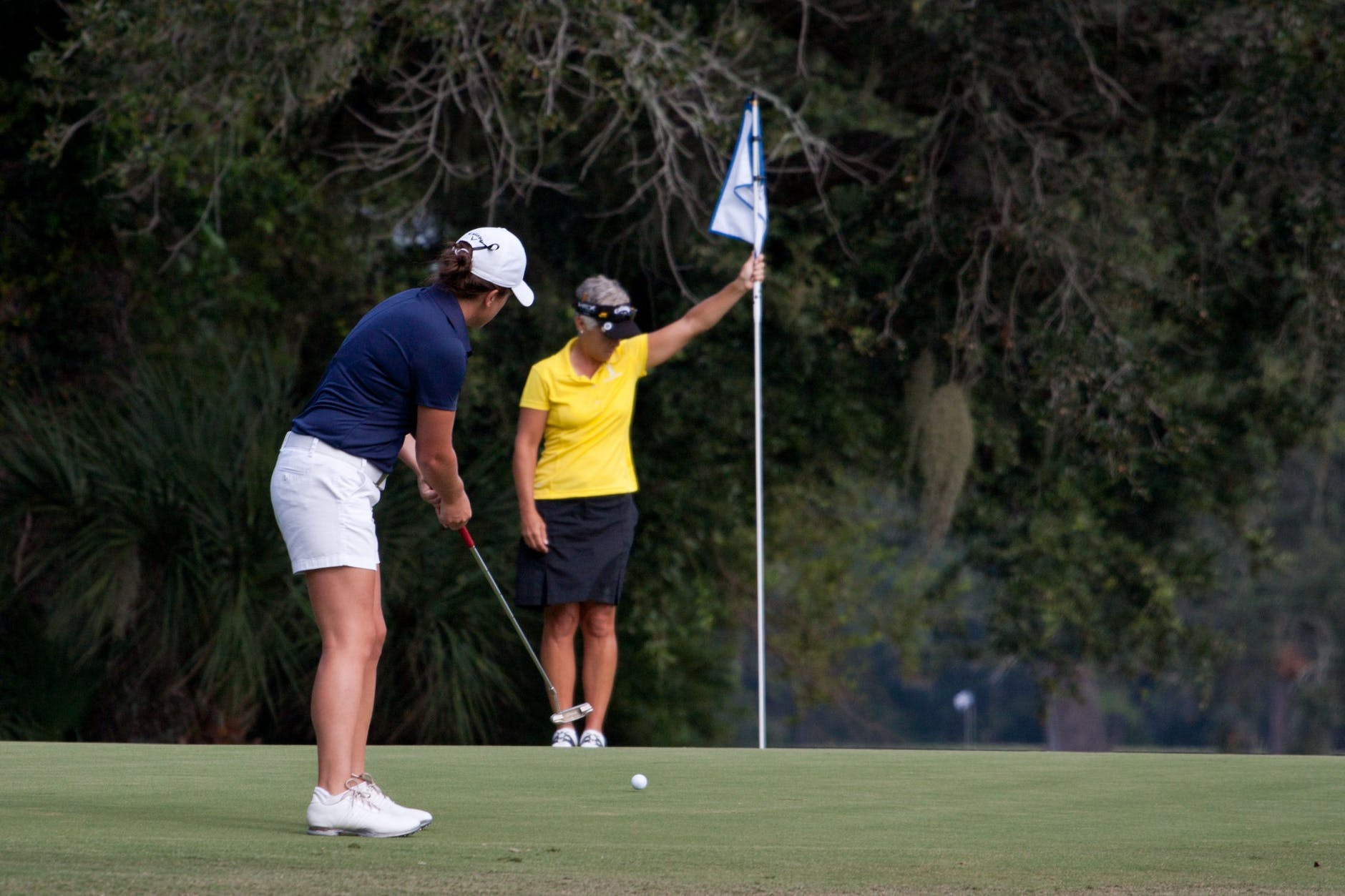 woman holding the flag and the one playing golf