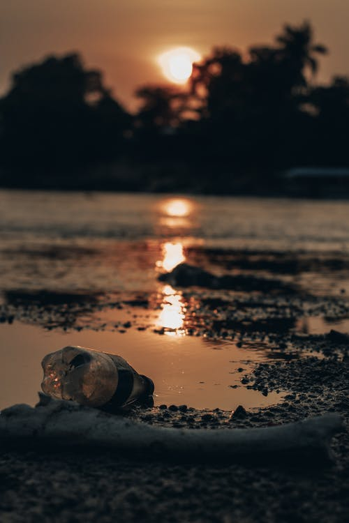 Ground level of plastic bottle on polluted sand beach with sun reflecting in water surface at sunset