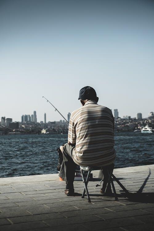 Man Sitting on Holding Fishing Rod