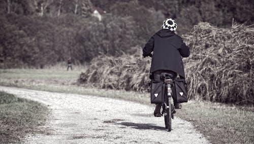 Person Biking in Dirt Road