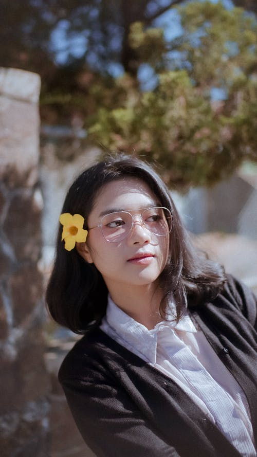 Lady Wearing Eyeglasses With Yellow Bell Flower On Hair