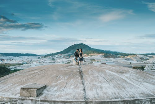 Two People on a Gray Cement Roof