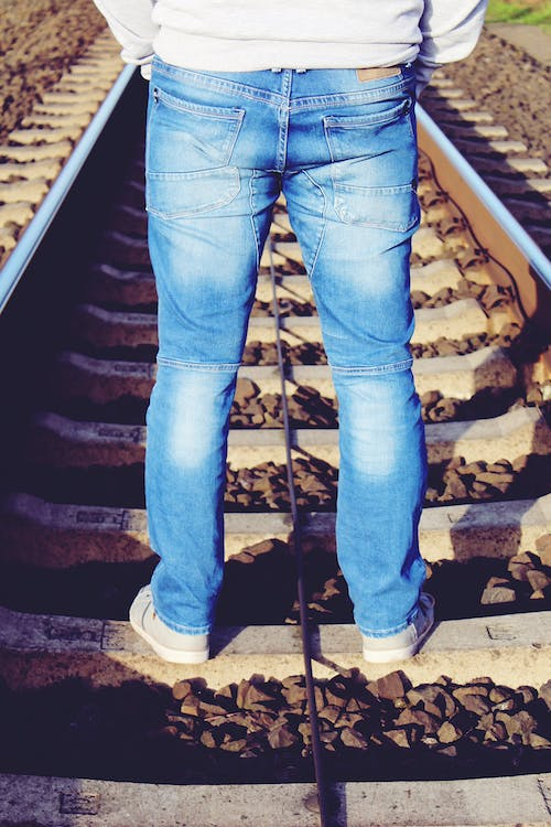 Person Wearing Blue Denim Pants While Standing on Brown Train Rail