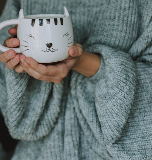 Unrecognizable female in warm long sleeved knit grey sweater with cup of hot coffee at home