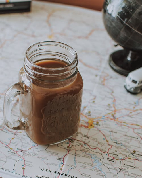 Glass jar of cocoa drink on map