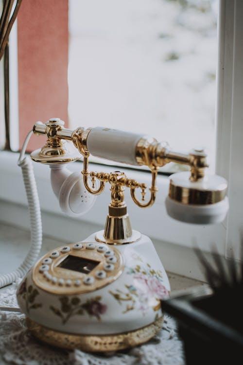 Retro telephone placed on plastic windowsill
