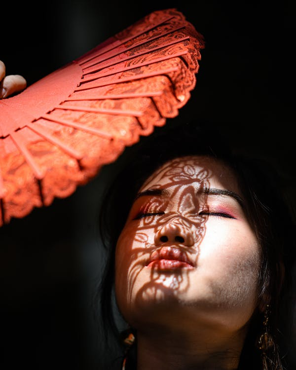 Photo of Woman Cover Her Face With Hand Fan