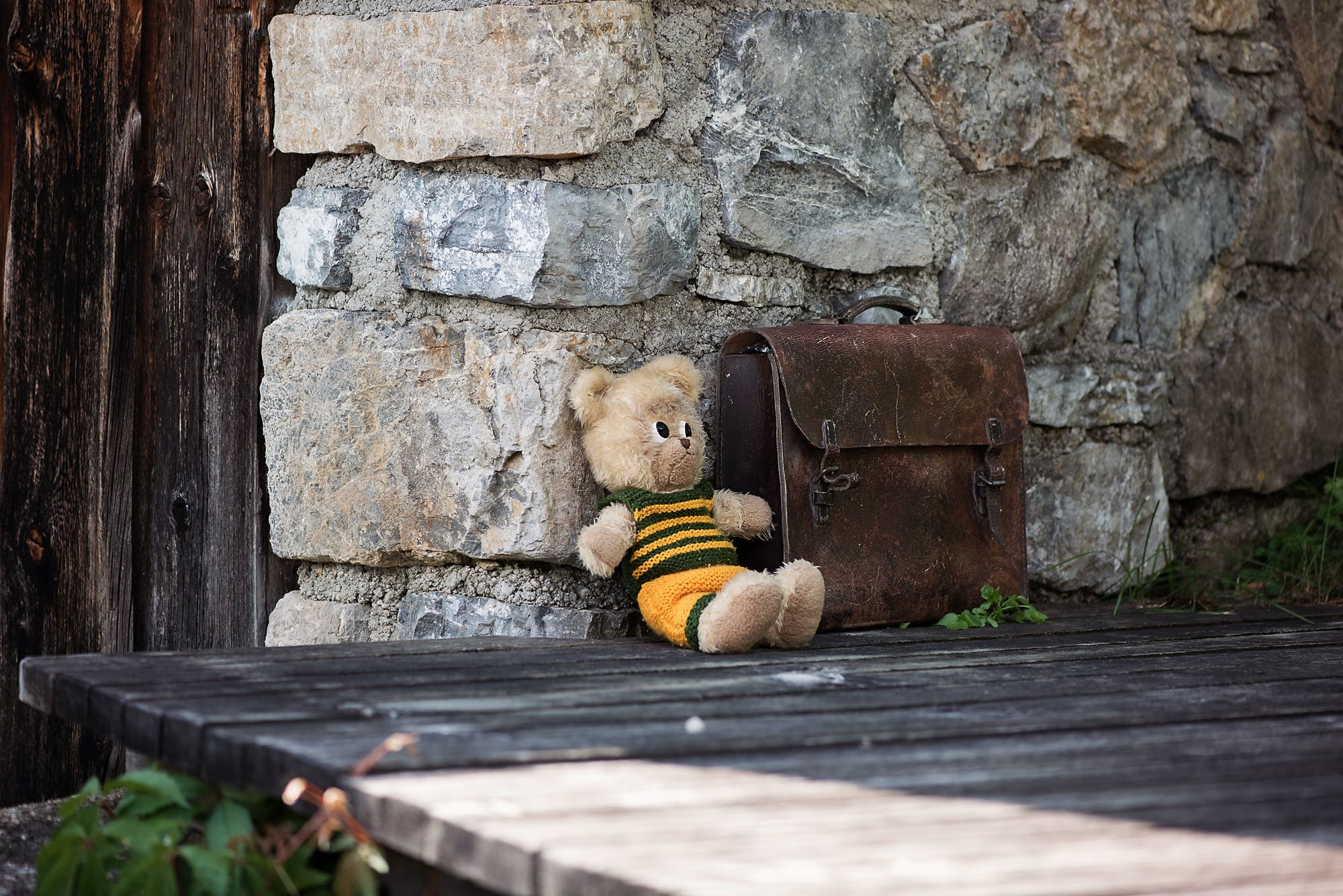 Brown Bear Plush Toy Leaning on Brown Concrete Wall
