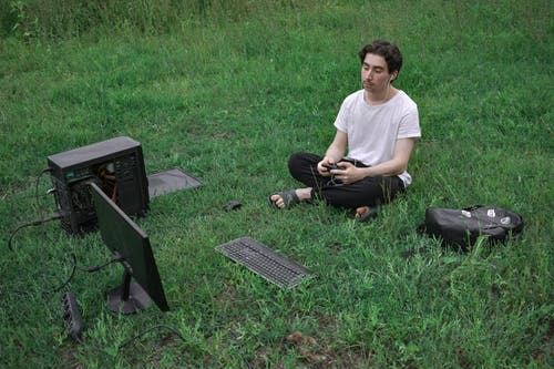 Man Sitting on Grass Using Computer