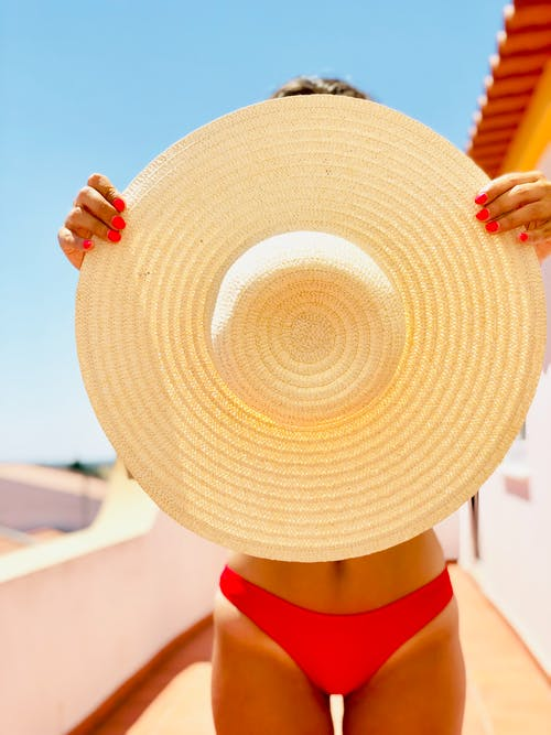 Photo of Woman Holding Straw Hat