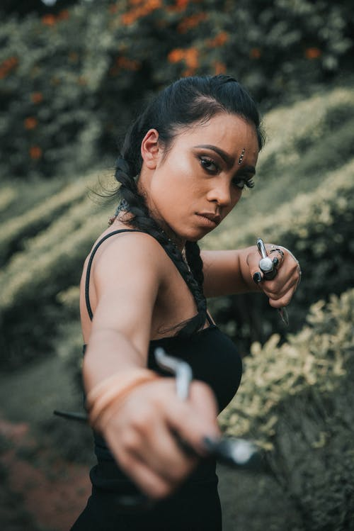 Concentrated ethnic woman pointing at camera with metal sticks