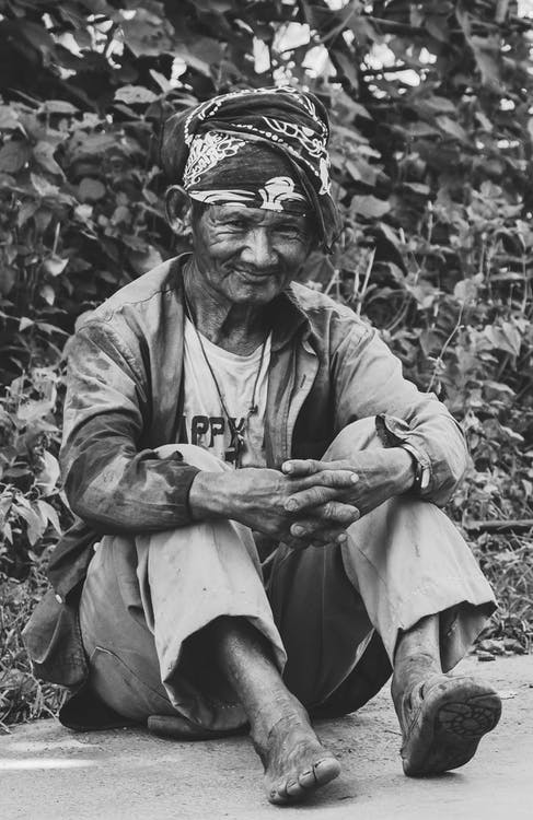 Grayscale Photography Of Old Man Sitting Near Plants