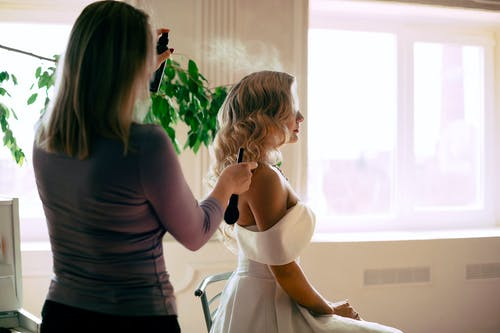 Hair Stylist Spraying Bride's Hair