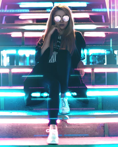 Woman Wearing Black and  Sunglasses Sitting Near Led Lights
