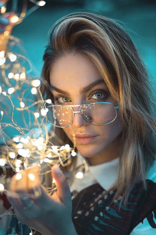 Close-up Photo of Woman Holding String Lights