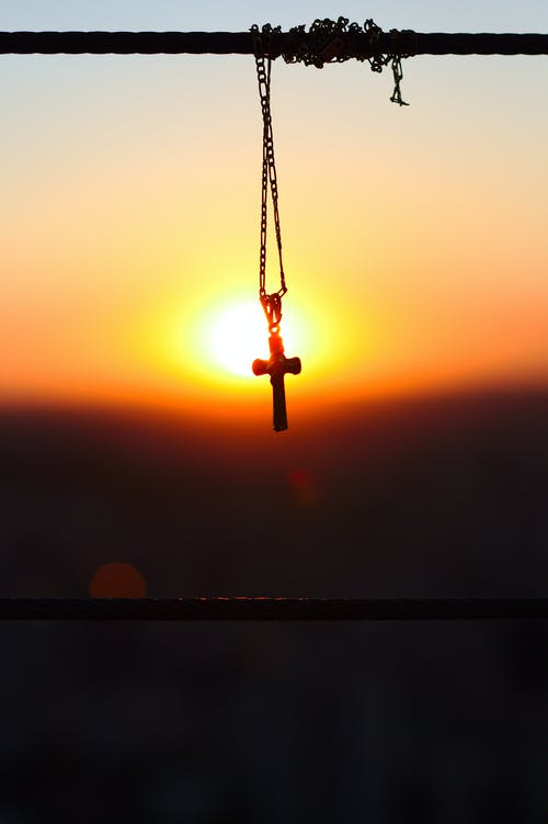 Silhouette Photography of Figaro Chain Necklace With Cross Pendant