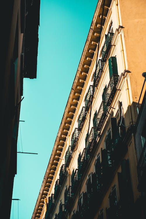 Безкоштовне стокове фото на тему «Будівля, жовтий будівлі, Захід сонця, світло та тінь»