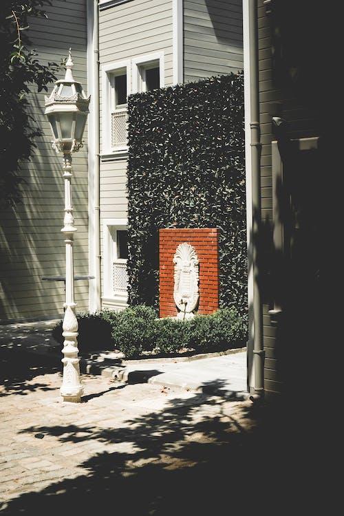 Безкоштовне стокове фото на тему «будівлі, світло полюса, тіні, фонтан»