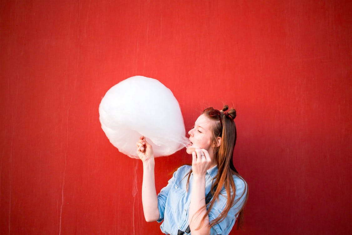 Woman In Blue Long Sleeved Shirt Eating Cotton Candy