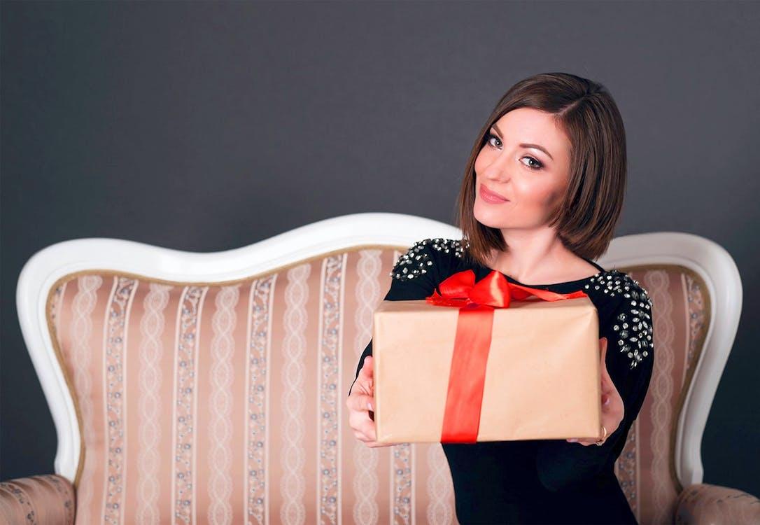 Woman Wearing Black Dress Holding A Gift