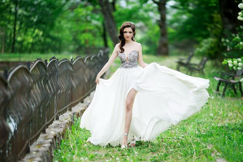 Woman in White and Silver Dress Posing Near a Fence