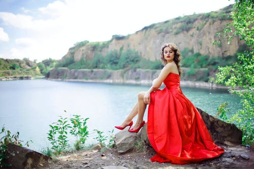 Woman Wearing Red Gown Sitting on Rock Near Body of Water