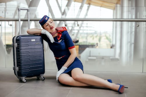 Woman Sitting On The Floor Beside Black Luggage