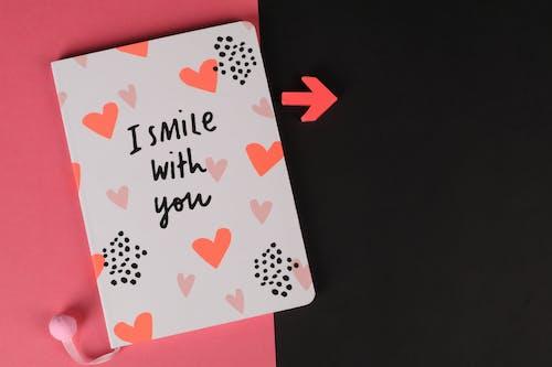 Gratis arkivbilde med jeg smiler med deg, notisbok, pil, rosa bakgrunn