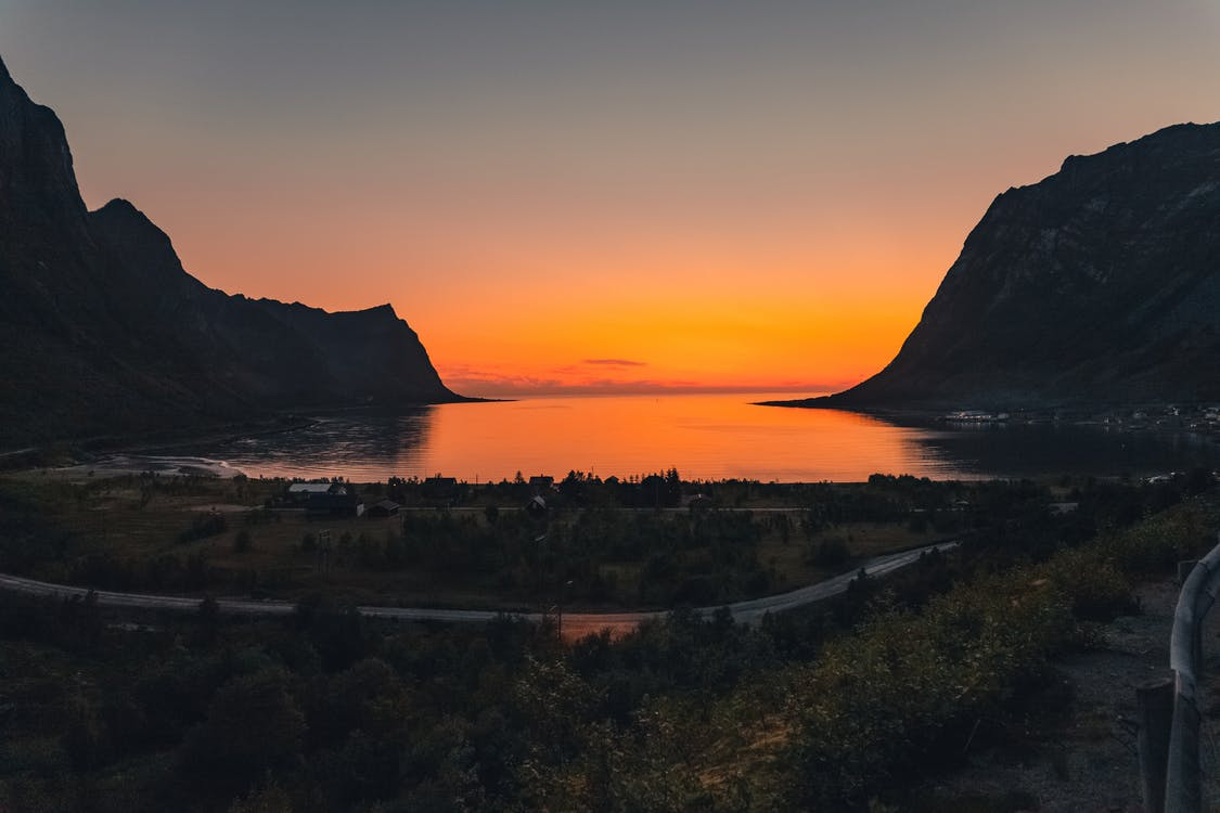 Sunset landscape of rocky mountains and calm sea