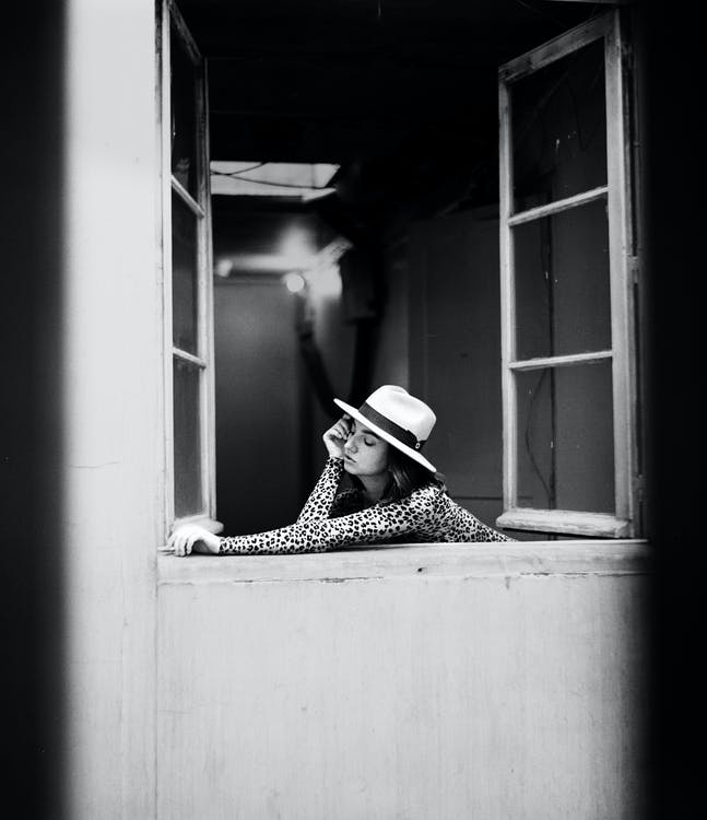 Grayscale Photography Of Woman Leaning On Open Window