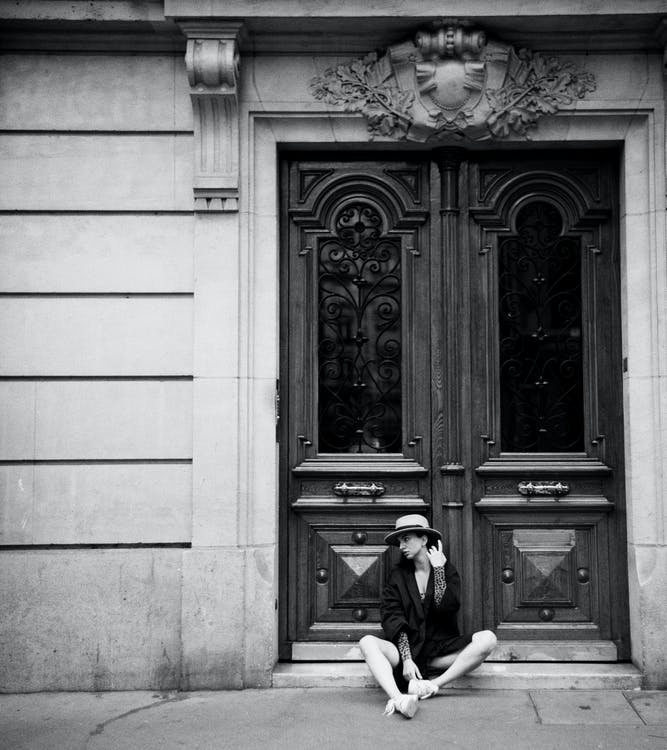 Monochrome Photo Of Woman Sitting In Front Of Door