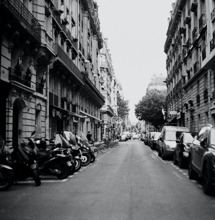 Grayscale Photo Of Vehicles Parked Outside Buildings